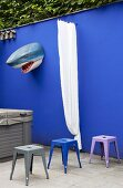 Colourful metal stools in front of shark's head and curtain on blue garden wall