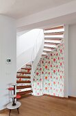 Spiral staircase decorated with retro-style floral wallpaper