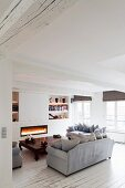 Fire in fireplace, opium table and white wooden floor in lounge of renovated period apartment