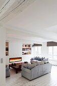 Loungebereich mit Kaminfeuer und Opiumtisch in renovierter Altbauwohnung mit weißem Dielenboden