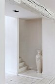 Floor vase at foot of simple white staircase behind partition wall