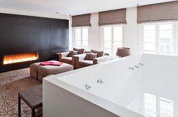 Eleganter Loungebereich mit Gaskamin auf Galerie mit weißer Brüstung