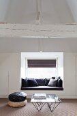 Gemütliche Sitznische vor Fenster zwischen weißen Einbauschränken im ausgebauten Dachgeschoss