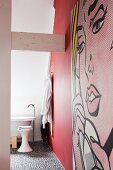 Ensuite bathroom with red wall, pebble floor and pop-art mural
