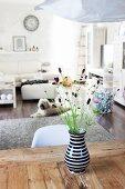 Wiesenblumenstrauß in schwarz-weißer Vase auf rustikalem Holztisch