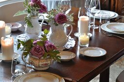 Flowers in jugs and tureen on set table