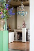 Glass artworks on white plinths, coloured glass chandelier and flowers in antique interior