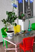 Small lemon tree on glass table surrounded by colourful chairs