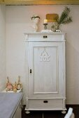Christmas decorations on white-painted vintage-style wooden cupboard