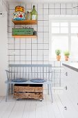 Grey wooden bench, wooden crate on castors and retro tins on wall-mounted shelves in white-tiled kitchen