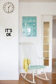 White rocking chair below framed picture and next to sliding door, motto on pennant and wall clock