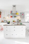 Kitchen island, retro scales and colourful tins in white fitted kitchen