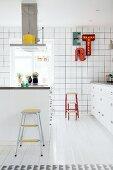 weiße Einbauküche mit bunten Farbakzenten, Kücheninsel und Leuchtbuchstaben als Wanddekoration
