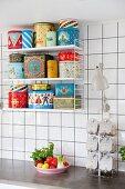 Verschiedene bunte Retro Metalldosen auf String-Regal in weiß gefliester Küche