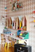 DIY play shop and house-shaped shelf units against diamond-patterned wallpaper