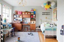 Retro Schrank in Jungenzimmer mit gemusterter Tapete, Spielzeug und skandinavischem Retro-Flair