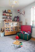 Toys tidied into retro cabinet with transparent drawer fronts in boy's bedroom