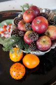 Apples, pine cones and fir sprigs next to oranges stuck with cloves