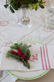 Table festively set with sprigs of fir and berries