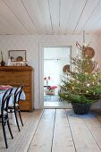 Decorated Christmas tree in basket in low-ceilinged interior