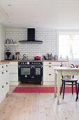 Dining area and vintage-style cooker in large country-house kitchen