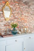 Gilt-framed mirror on rustic brick wall above family photos on pale blue sideboard