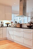 Vintage utensils in elegant, L-shaped fitted kitchen with extractor hood