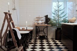 Ladder, free-standing bathtub, sewing-machine table and Christmas tree in black and white bathroom