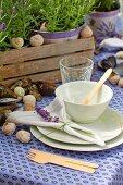 Gedeckter Gartentisch mit lila Tischtuch und weissem Geschirr, Tischdekoration mit Muschelschalen und Schneckengehäuse