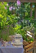 Gedeckter Gartentisch mit Lavendel und Schneckengehäuse dekoriert