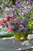 Romantisches Blumengesteck auf Vintage Gartentisch