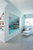 Kinderzimmer mit eingebautem Bett, Regalen und Loungesessel auf grauem Teppichboden