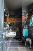Black-tiled bathroom with shower area