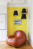Lounge-Ledersessel vor gelber Wand und schwarzen Lampenschirmen in restaurierter Altbauwohnung