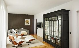 Glass-fronted cabinet, Eames Lounge Chair and sofa in elegant living area
