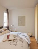 Bedspread and scatter cushions with mottos on double bed in front of Baroque drawing
