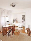 Table lamp on retro desk and metal chair on rug with view into bedroom through open doorway
