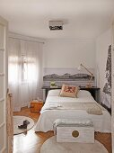 Black and white photos and scatter cushion on bed and wooden trunk on round rug in bedroom
