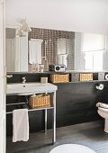 Washstand against black wall cladding with storage baskets on shelf below large mirror