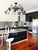 Counter below designer lamp with multiple anglepoise arms in elegant kitchen with exotic-wood parquet floor
