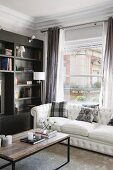 Scatter cushions on white sofa and coffee table in front of window and shelving