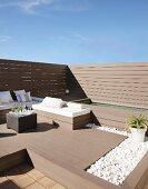 Elegant benches with white cushions and small bed of pebbles on sunny roof terrace