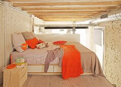 Sleeping area with orange accents below exposed beams and ventilation ducts in loft apartment