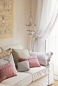 Piles of various scatter cushions on sofa in corner of romantic room