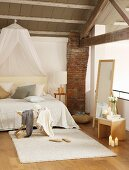 Rustic beams and brick pillar in gallery bedroom of loft apartment