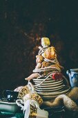 Antique dolls tied together on stack of crockery