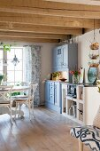 Rustic wood-beamed ceiling and wooden floor in cosy country-house kitchen