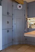 Corner cupboard in country-house-style fitted kitchen with blue-grey fronts