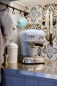 Pale blue retro espresso machines in front of ornamental, floral, tiled splashback in country-house kitchen