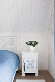 Vintage white bedside cabinet next to bed with vintage headboard below wood-panelled sloping ceiling